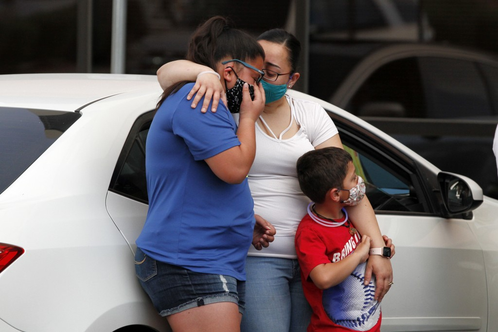 In this Thursday, May 21, 2020 photo, widow Jessica Coco Garcia, hugs her children at a memorial in the Del Sol Medical Center parking lot for father ...