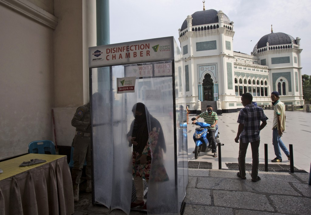 A Muslim women enters a disinfection chamber installed at the gate of Al Mashun Grand Mosque as a precaution against the new coronavirus outbreak afte...
