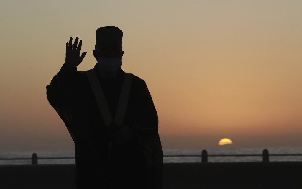 A senior Muslim cleric observes the skies over Cape Town, South Africa, Saturday, May 23 2020 in the hope of spotting the new moon to mark the end of ...