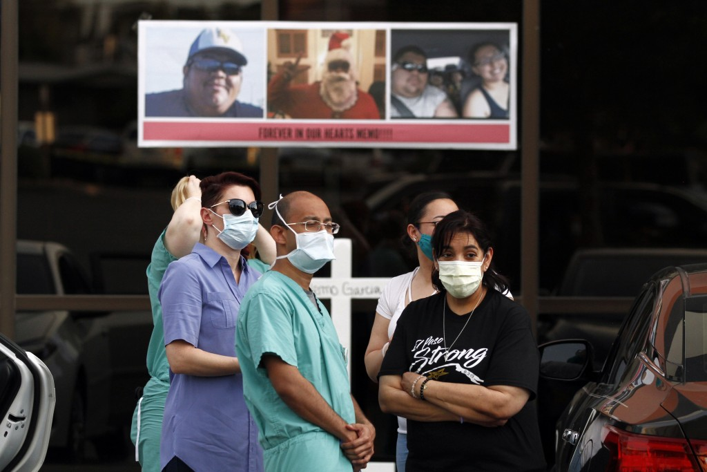 "In this Thursday, May 21, 2020 photo, mourners wear masks to prevent the spread of COVID-19 at a memorial for Walmart shooting victim Guillermo ""Memo""..."