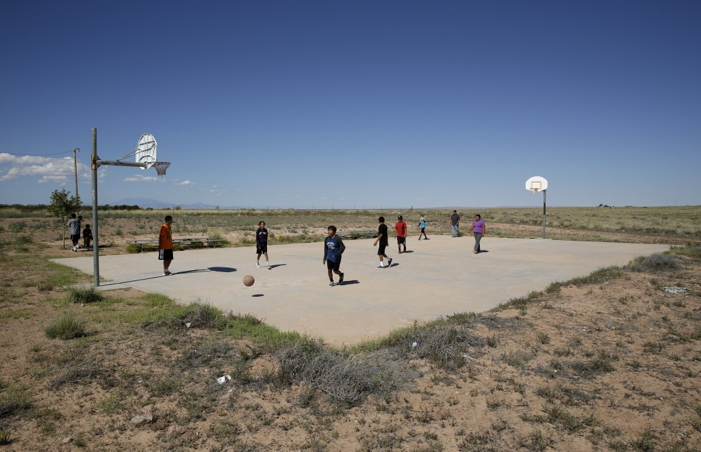 FILE - In this Sept. 25, 2014, file photo, students play basketball at Little Singer Community School in Birdsprings, Ariz., on the Navajo Nation. Bas...
