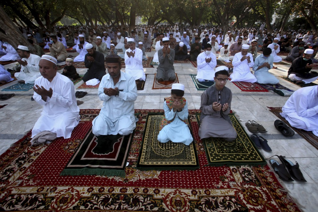 Muslims attend Eid al-Fitr prayer in an open area in Peshawar, Pakistan, Sunday, May 24, 2020. Millions of Muslims across the world are marking a mute...