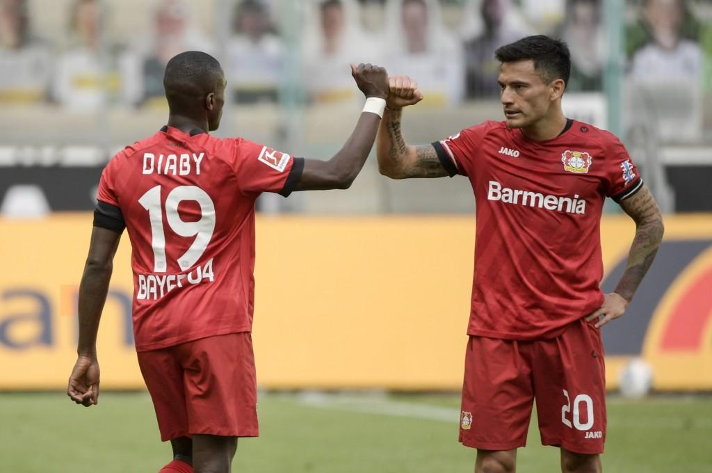 Leverkusen's French forward Moussa Diaby, left, and teammate Charles Mariano Aranguiz celebrate after the German Bundesliga soccer match between Borus...