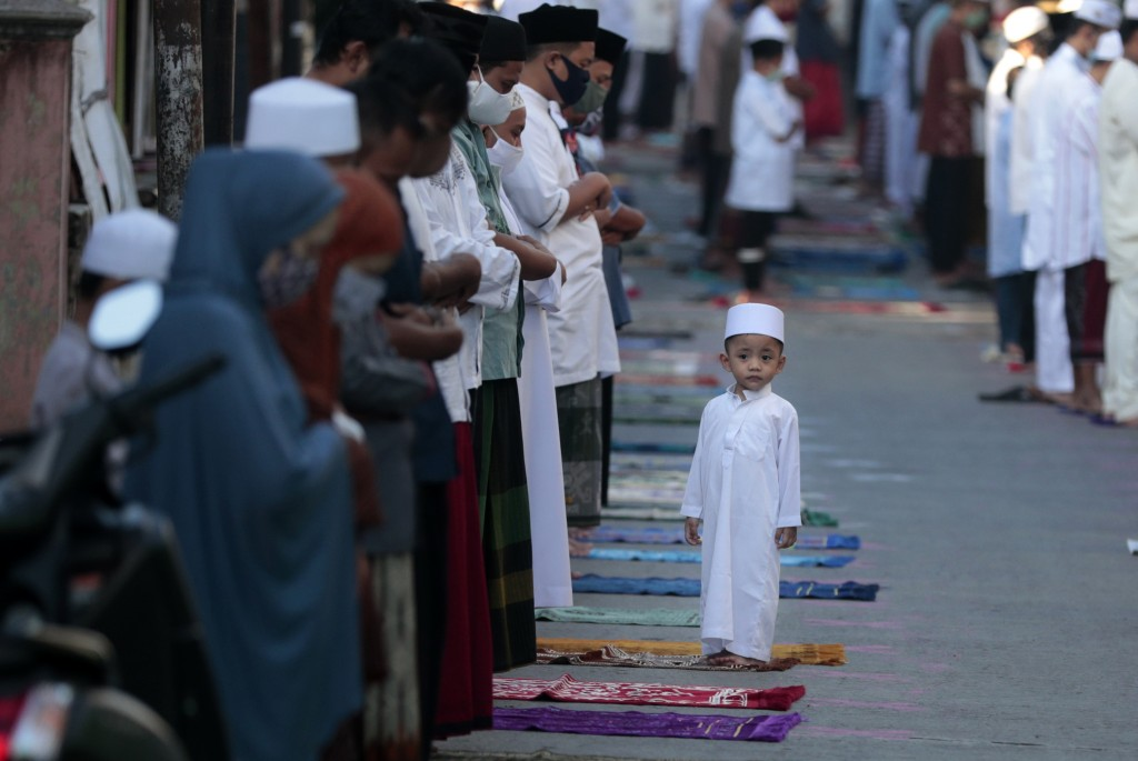 A boy stands as his parents perform an Eid al-Fitr prayer marking the end of the holy fasting month of Ramadan amid concerns of the new coronavirus ou...