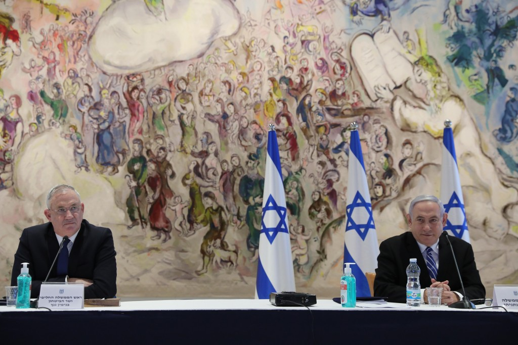 Israeli Prime Minister Benjamin Netanyahu, right, and Defense Minister Benny Gantz attend the first Cabinet meeting of the new government at the Chaga...