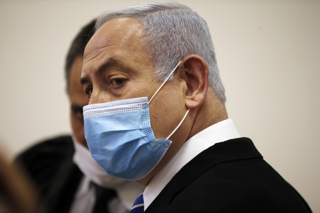Israeli Prime Minister Benjamin Netanyahu, wearing a face mask in line with public health restrictions due to the coronavirus pandemic, stands inside ...