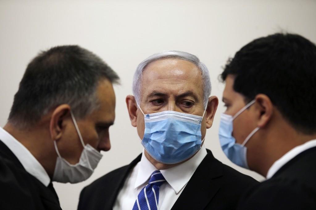 Israeli Prime Minister Benjamin Netanyahu, wearing a face mask in line with public health restrictions due to the coronavirus pandemic, looks at his l...