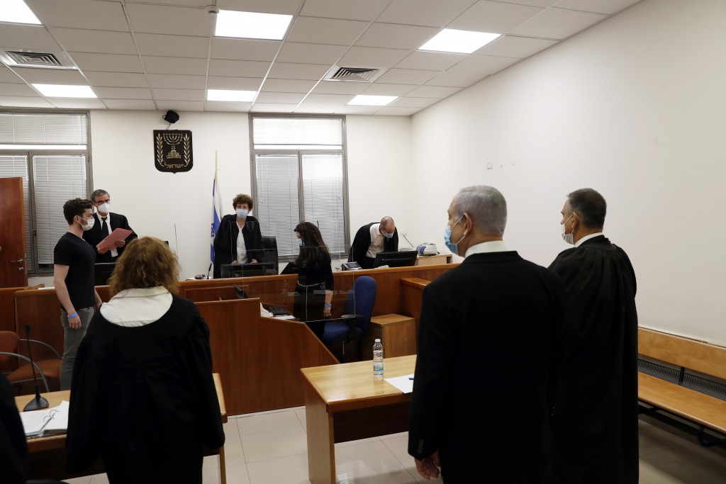 Israeli Prime Minister Benjamin Netanyahu, second right, stands while the judges enter the court room as his corruption trial opens at the Jerusalem D...