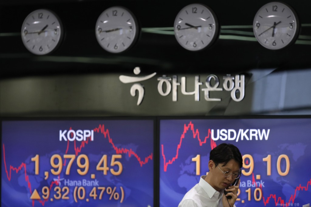 A currency trader talks on the phone near the screens showing the Korea Composite Stock Price Index (KOSPI), left, and the foreign exchange rate betwe...