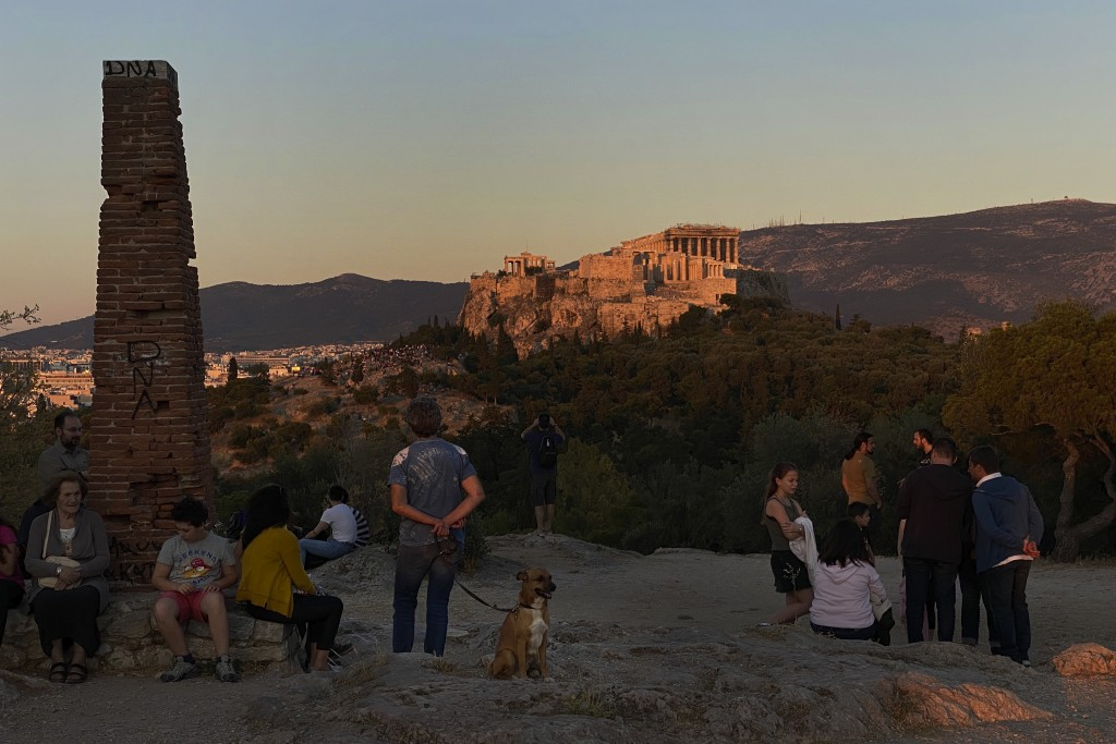 People gather near Pnyx as at the background stands the ancient Acropolis hill, with the ruins of the fifth century BC Parthenon temple in Athens, Sun...