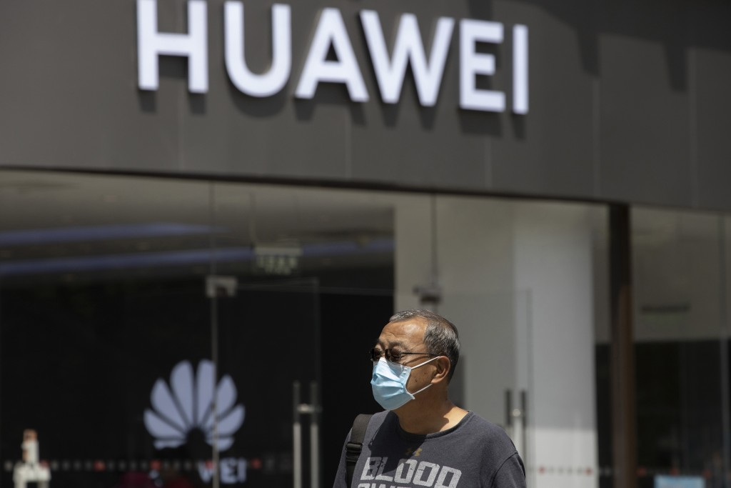FILE - In this May 18, 2020, file photo, a man wearing a face mask to protect against the coronavirus walks past a Huawei retail store in Beijing. One...