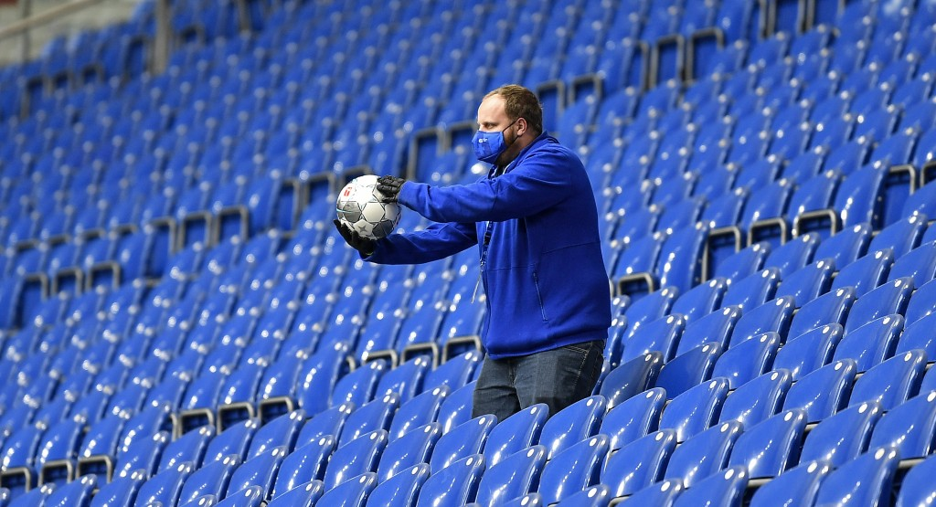 A ball boy gets a ball from the empty tribune prior the German Bundesliga soccer match between FC Schalke 04 and FC Augsburg at the Veltins-Arena in G...