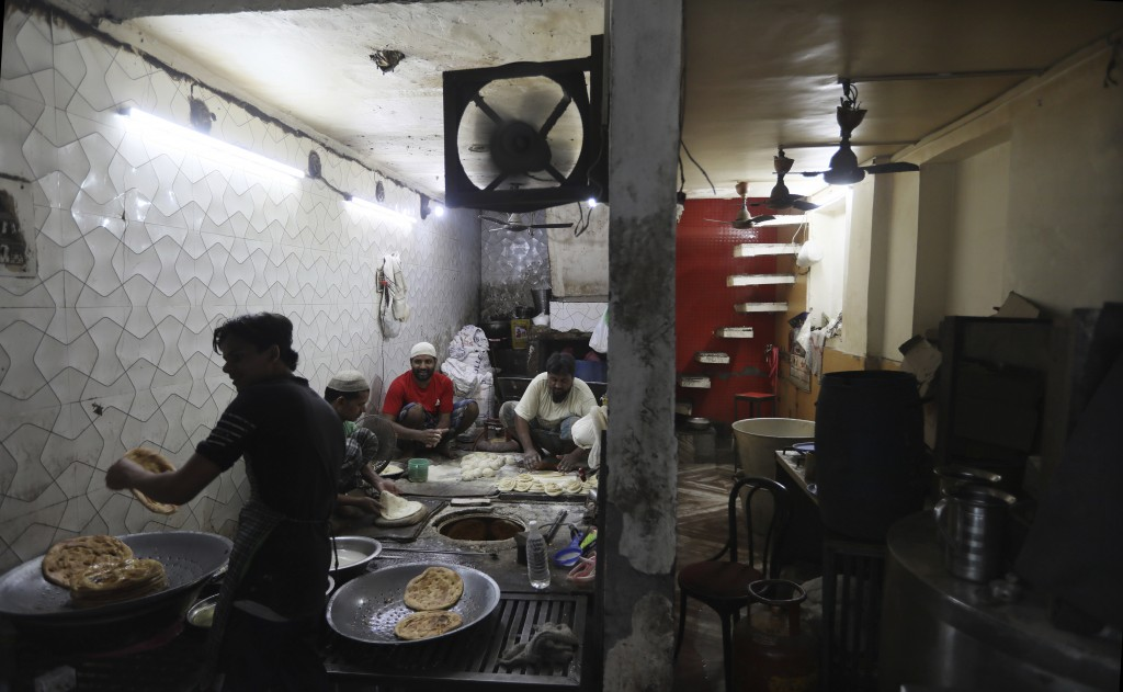 Indian Muslims make sweet flat bread during Eid al-Fitr near the Jama Mosque at the old quarters of New Delhi, India, Monday, May 25, 2020. The holida...