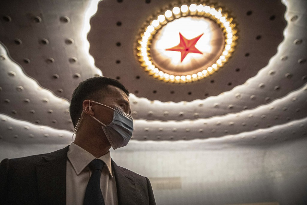 Security official wearing protective face mask stands guard before China's National People's Congress.
