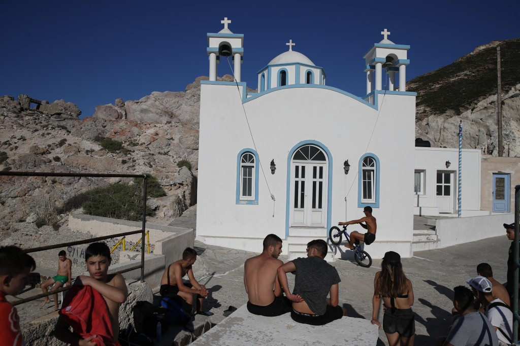 Children gather in front of a Greek Orthodox church on the Aegean Sea island of Milos, Greece, on Sunday, May 24, 2020. Greece's long-awaited tourist ...