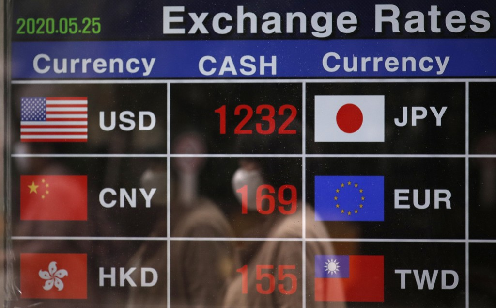 A woman wearing a face mask is reflected on an electronic foreign currency exchange rates in downtown Seoul, South Korea, Monday, May 25, 2020. Asian ...