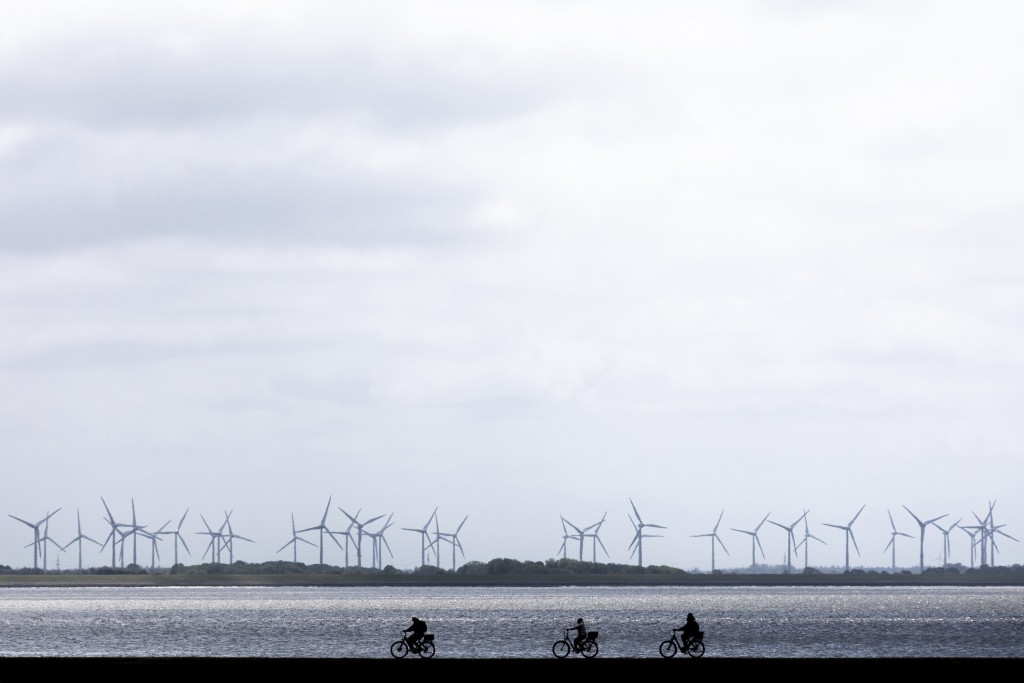 Cyclists ride their bicycles over a dyke by the sea at the island Norderney, Germany, Monday, May 25, 2020.  Germany's northern states are starting to...