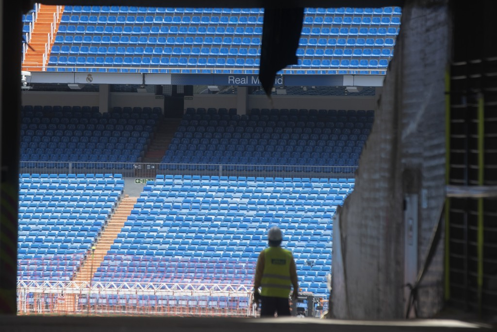 Workers walk into Real Madrid's Santiago Bernabeu stadium in Madrid, Spain, Monday, May 25, 2020. Spanish league clubs are now allowed to train with g...