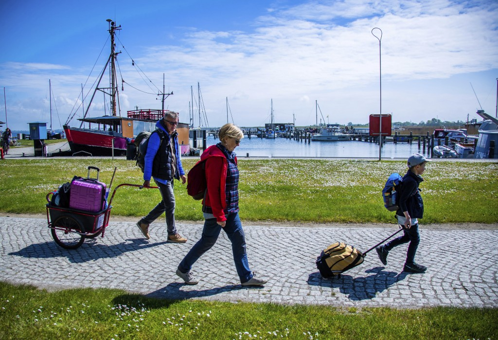 Tourists with backpacks and suitcases arrives at the port of Kloster on the Baltic island Hiddensee in Vitte, Germany, Monday May 25, 2020. In German ...