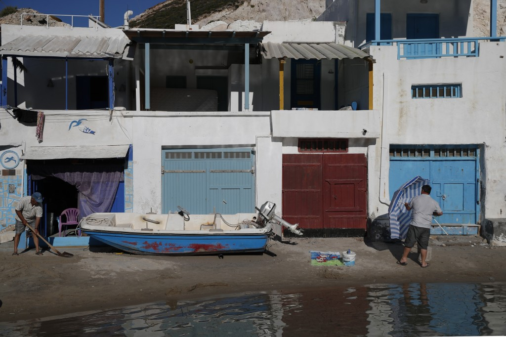 A man closes an umbrella as another one cleans the sand in front of small houses, some of them are used for summer accommodation, on the Aegean Sea is...