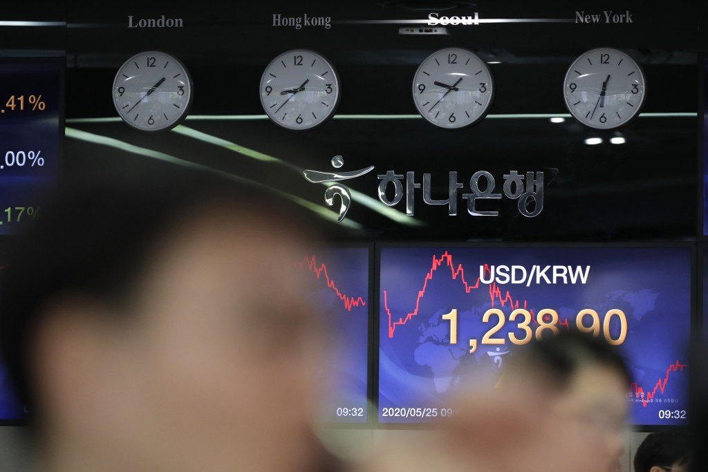 A currency trader talks on the phone near the screen showing the foreign exchange rate between U.S. dollar and South Korean won at the foreign exchang...