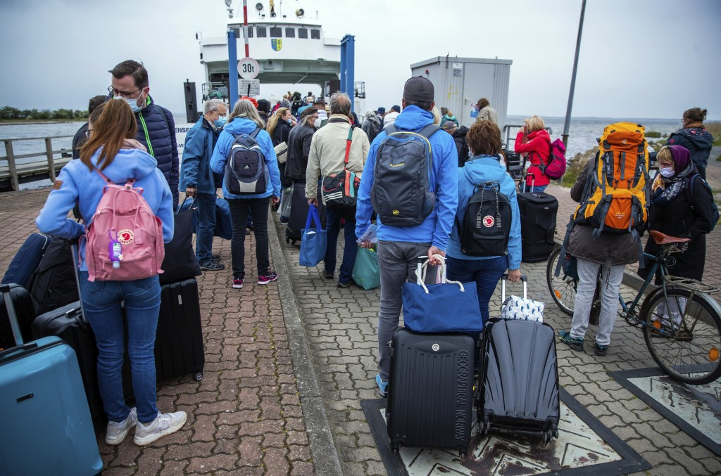 25 May 2020, Mecklenburg-Western Pomerania, Schaprode: Tourists with backpacks and suitcases wait on a pier for transport with a ferry to the Baltic i...