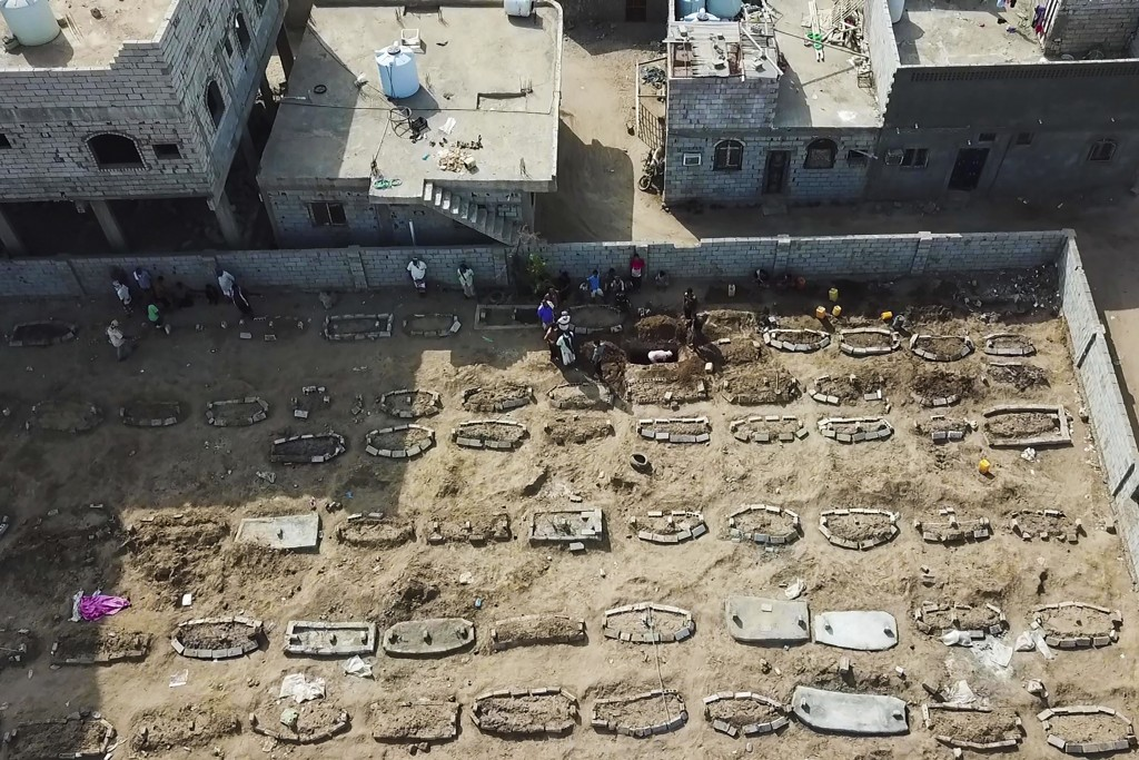 In this May 21, 2020, photo, grave diggers bury bodies at Radwan Cemetery in Aden, Yemen. At the cemetery in Yemen's largest southern city, dozens of ...