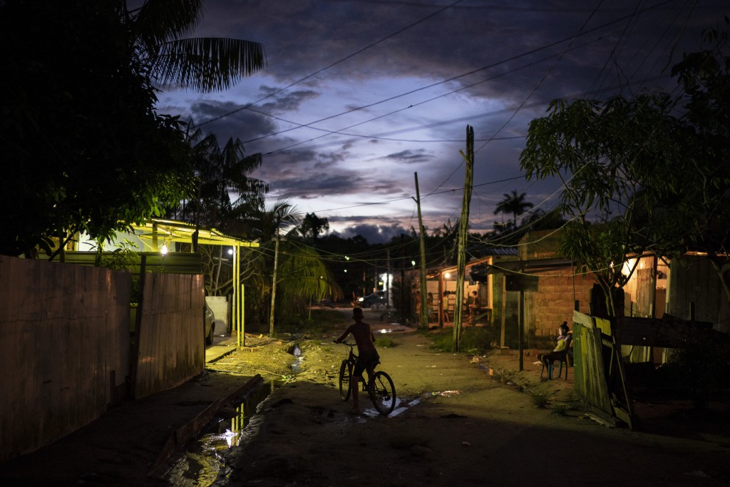 A boy rides his bike at dusk through the Park of Indigenous Nations community, where many residents have fallen ill with symptoms of the new coronavir...
