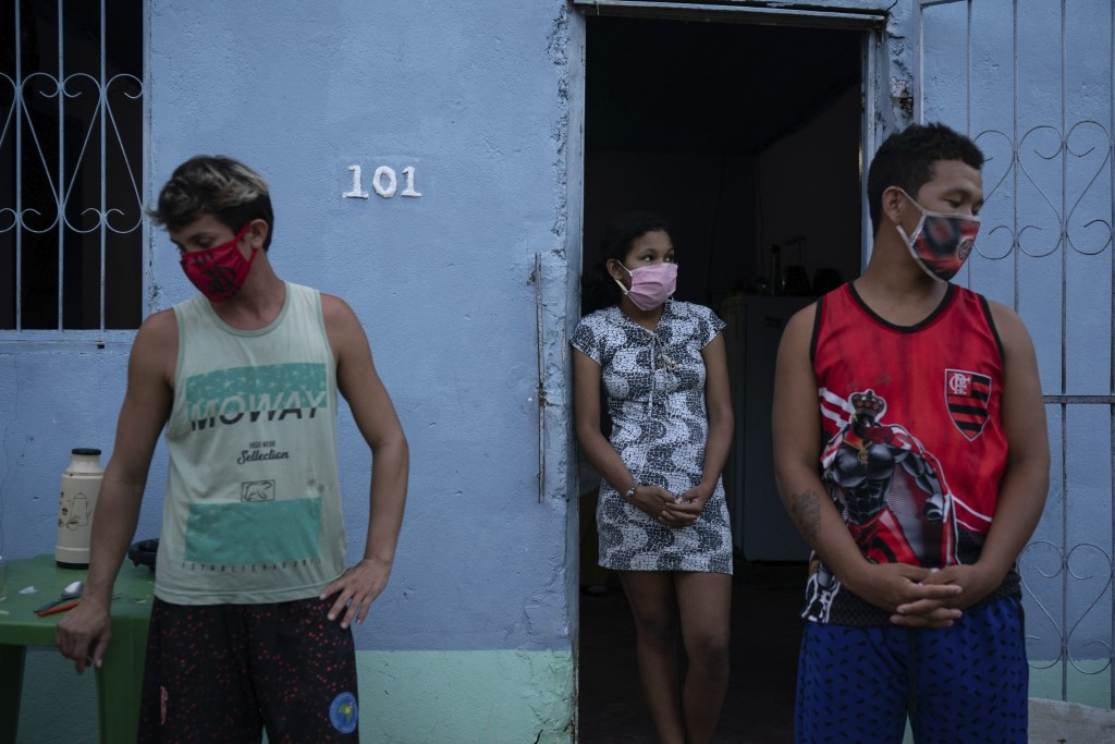Caregiver Leandro Beiton, left, and relatives of the late Edgar Silva, wearing face masks amid the new coronavirus pandemic, stand by after his body w...