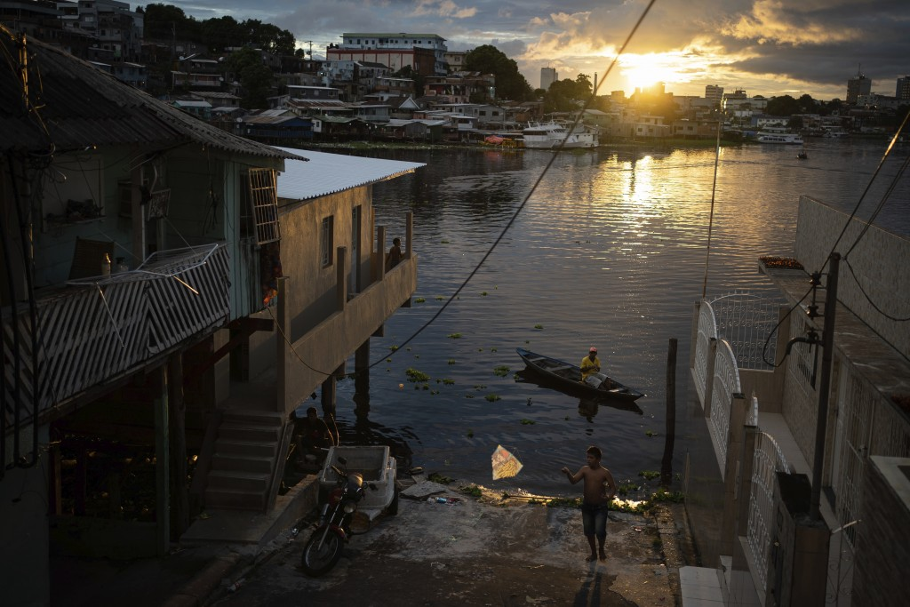 A boy flies a kite by the riverside in Manaus, Brazil, Sunday, May 24, 2020. Per capita, Manaus is Brazil's major city hardest hit by COVID-19. (AP Ph...