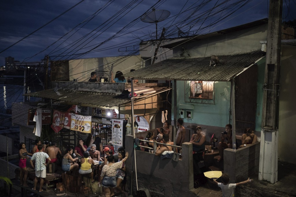 People gather outside a bar in Manaus, Brazil, Sunday, May 24, 2020, amid the new coronavirus pandemic. Although health experts warn that the pandemic...