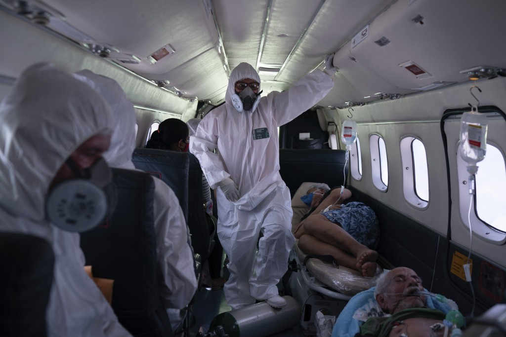 Nurse Janete Vieira, center, and Doctor Daniel Siqueira monitor COVID-19 patients onboard an aircraft as they are transferred from Santo Antônio do Iç...