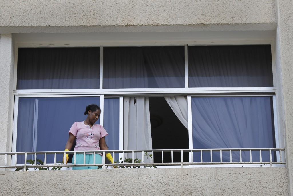 In this Saturday, May 23, 2020 photo, an Ethiopian domestic worker cleans her employer's balcony, in Beirut, Lebanon. Some 250,000 registered migrant ...