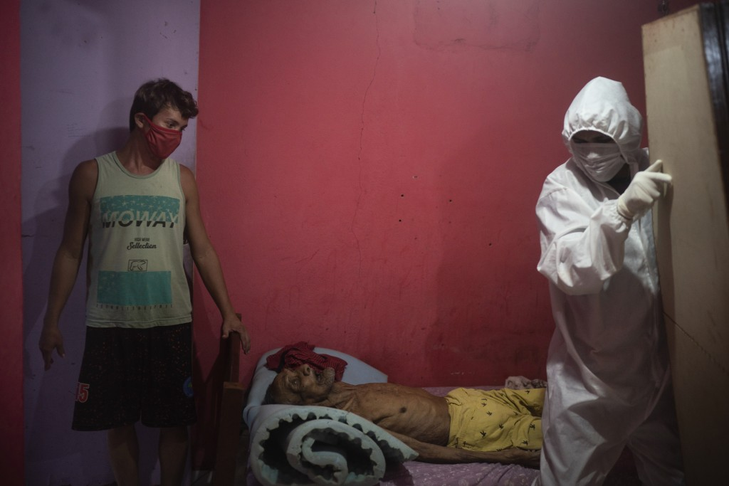 A worker from the SOS Funeral service, wearing protective gear amid the new coronavirus pandemic, is helped by caregiver Leandro Beiton as he prepares...