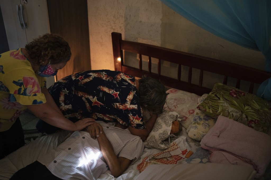 Relatives mourn over the body of Luis da Silva, 82, who had pre-existing health conditions and died at home after suffering from shortness of breath i...