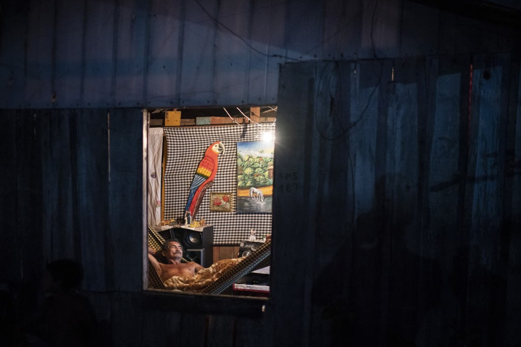 A man rests in a hammock inside his home at the Park of Indigenous Nations community, where many residents fell ill with symptoms of the new coronavir...