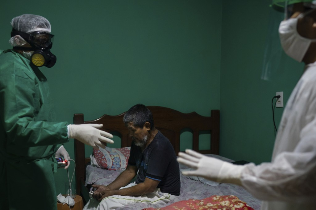 Plinio dos Santos, 65, who was having difficulty breathing, sits on his bed as emergency worker Wanden Nascimento, left, checks his oxygen saturation ...