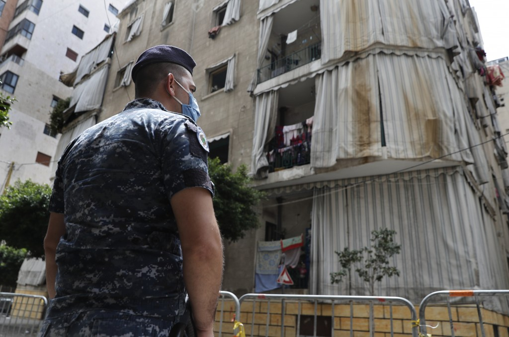 In this Saturday, May 23, 2020 photo, a Lebanese policeman is deployed to enforce isolation outside a building where dozens of foreign workers living ...