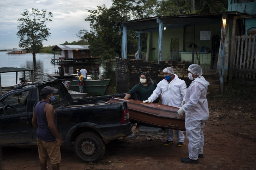 SOS Funeral workers move a coffin holding the body of an 86-year-old woman who lived by the Negro River and who is suspected of dying of COVID-19, nea...