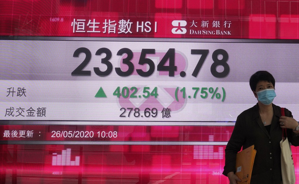 A woman wearing face mask walks past a bank electronic board showing the Hong Kong share index at Hong Kong Stock Exchange Tuesday, May 26, 2020. Asia...