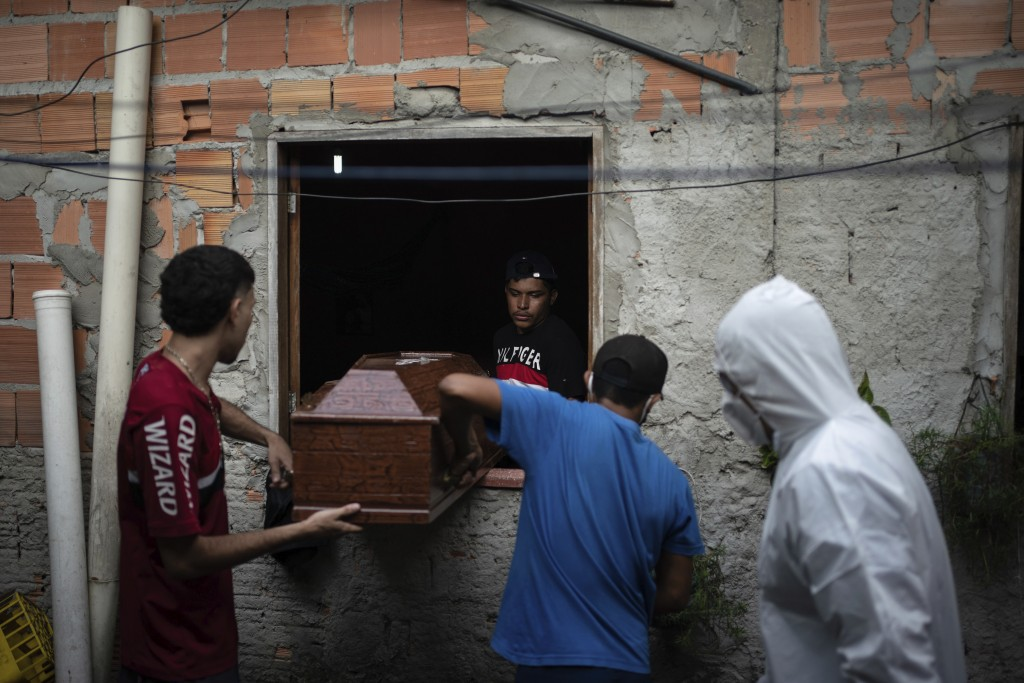 Relatives help a SOS Funeral worker, wearing protection equipment amid the new coronavirus outbreak, remove the body of Eldon Cascais from his home in...