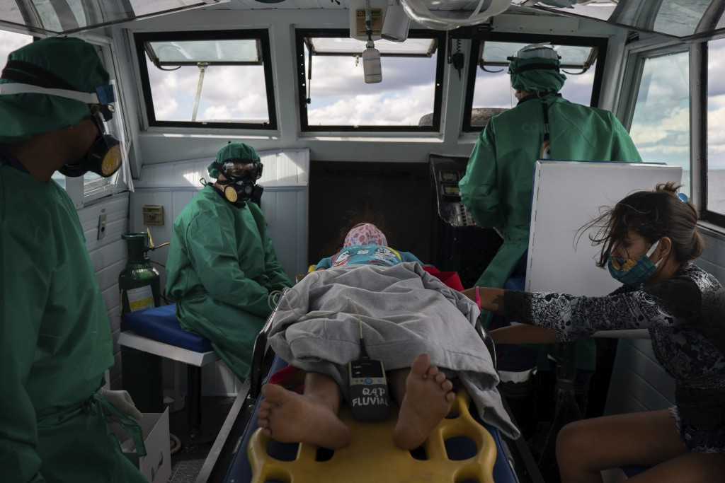 Fluvial emergency workers transfer by boat a 10-year-old suspected COVID-19 patient from a riverside community to a hospital in Manaus, Brazil, Friday...
