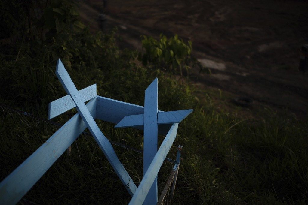 Painted wooden crosses lay on the roadside of a new section of the Nossa Senhora Aparecida cemetery in Manaus, Brazil, Saturday, May 16, 2020. The new...