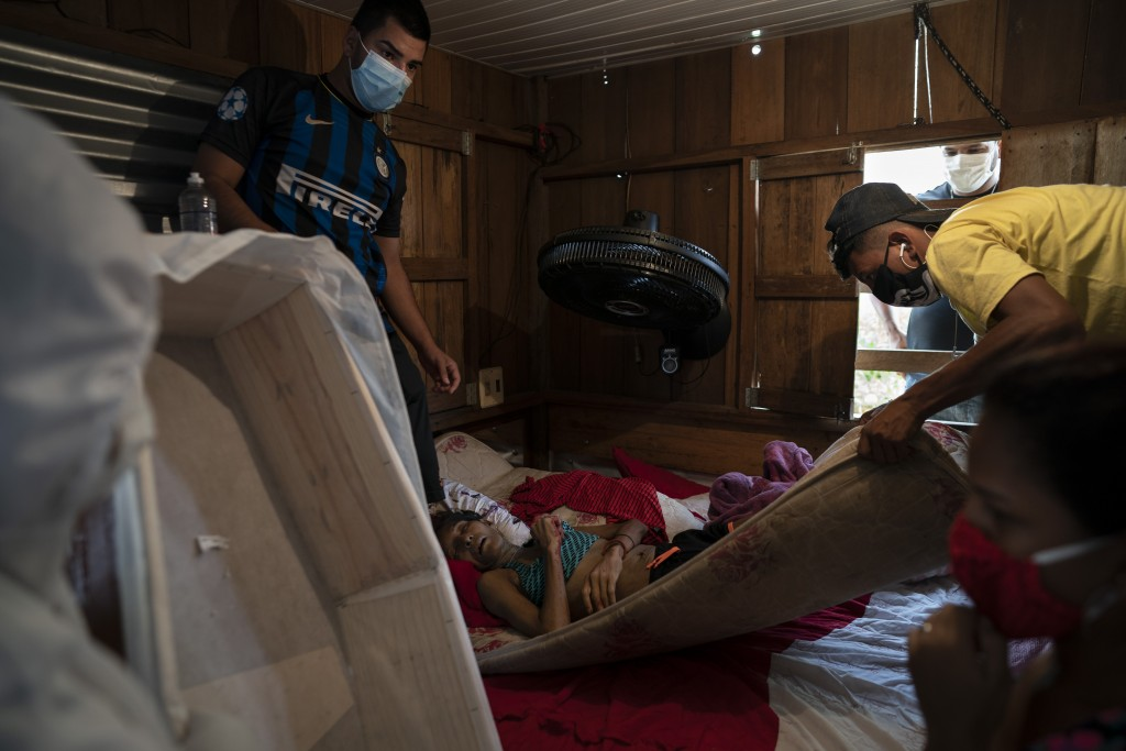 The sons of 42-year-old Leivane Bibiano help a SOS Funeral worker remove their mother's body amid the new coronavirus pandemic in Manaus, Brazil, Tues...