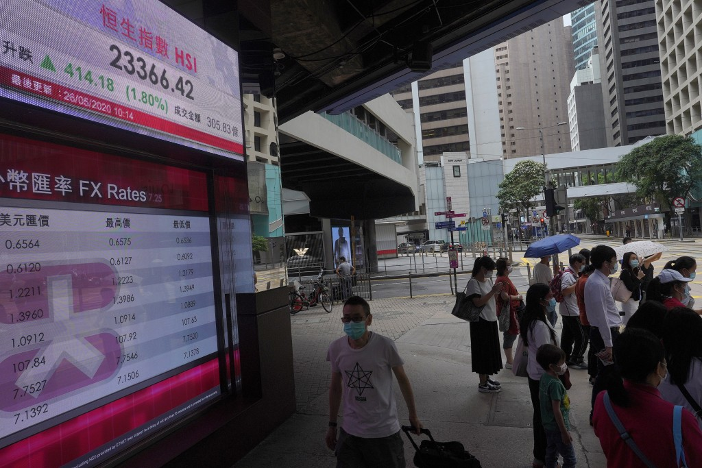 People wearing face masks stand near a bank electronic board showing the Hong Kong share index at Hong Kong Stock Exchange Tuesday, May 26, 2020. Asia...