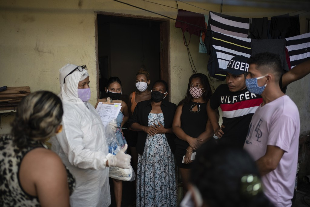 Relatives and friends of the late Eldon Cascais talk to a SOS Funeral worker wearing protection equipment amid the new coronavirus pandemic in Manaus,...