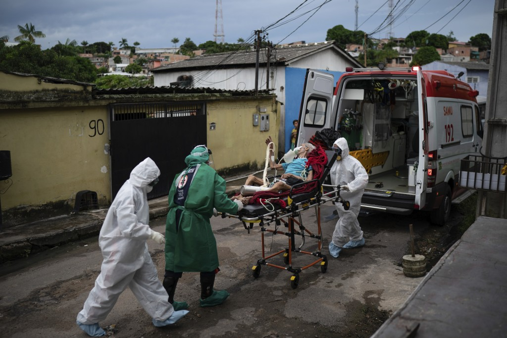 Emergency workers transfer an elderly patient, suspected of having COVID-19, to a hospital in Manaus, Brazil, Wednesday, May 13, 2020. Per capita, Man...