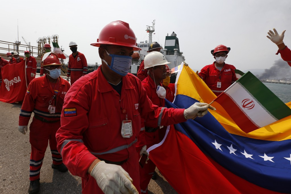 A Venezuelan oil worker holding a small Iranian flag attends a ceremony for the arrival of Iranian oil tanker Fortune at the El Palito refinery near P...