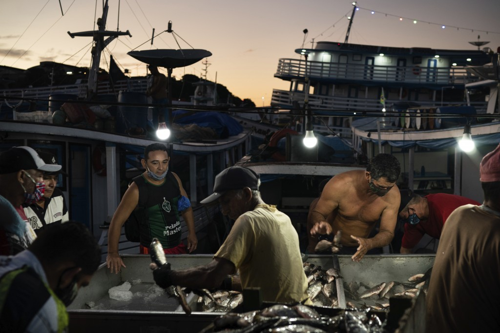 Men gather at a fish market in Manaus, Brazil, May 22, 2020. Although health experts warn that the COVID-19 pandemic is far from over in Manaus, or ac...