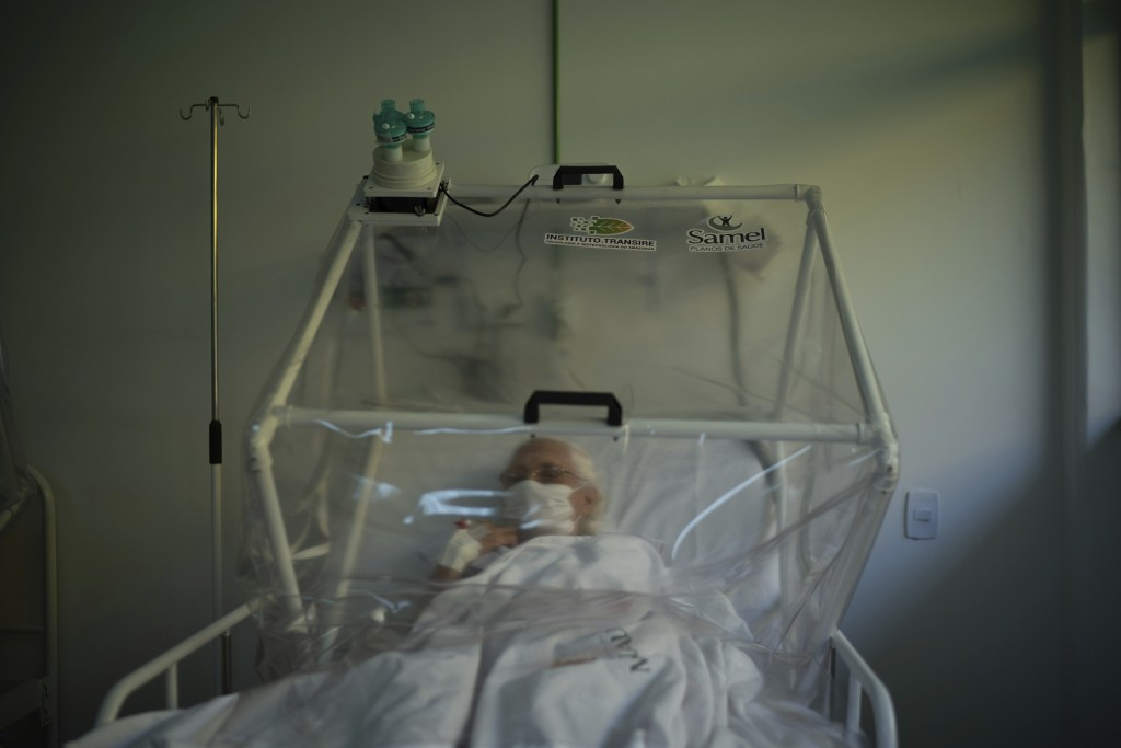 An elderly COVID-19 patient is treated inside a non-invasive ventilation system named the Vanessa Capsule at a municipal field hospital Gilberto Novae...